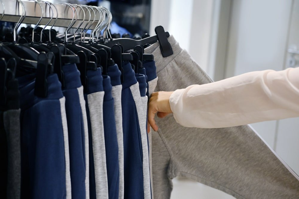Person going through a rack of sweatpants on hangers