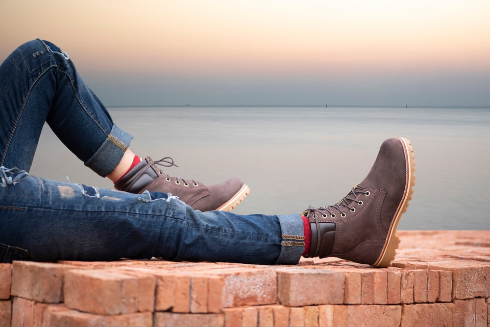 Person wearing boots with a sunset in the background