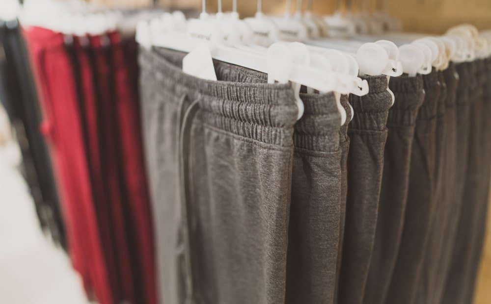 Multiple pairs of sweatpants hanging on a clothing rack