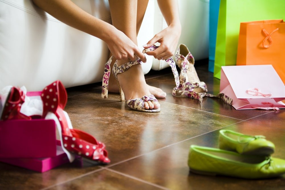 Close up of a person's feet as they try on high heels with other pairs of shoes all around