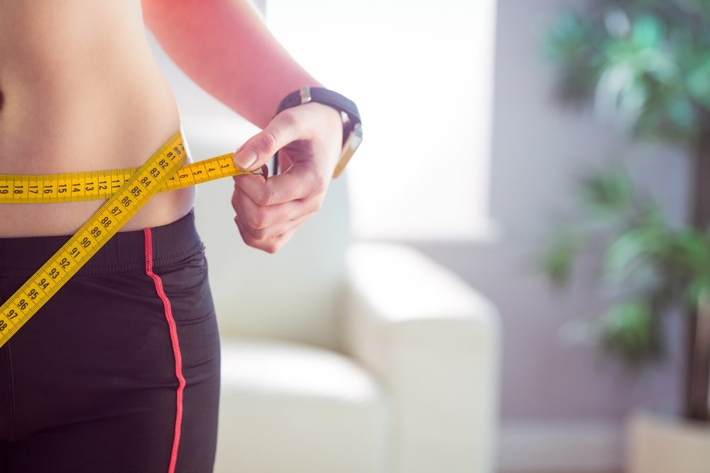Person measuring their waist with a tape measure